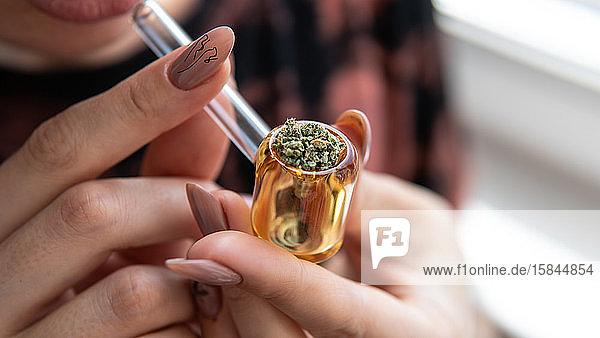 europäisches mädchen raucht marihuana durch eine glasröhre. cannabis sm