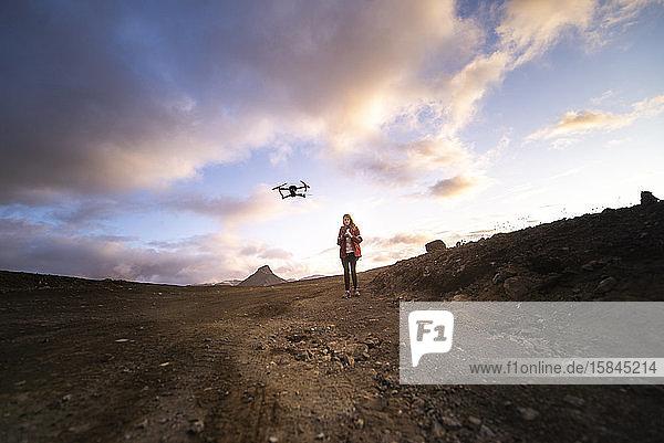 Silhouette einer Frau  die bei Sonnenuntergang eine Drohne kontrolliert und steuert