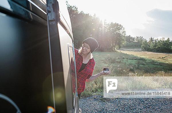 Frau  die Kaffee in der Hand hält  während sie sich im Sommer lächelnd aus einem Wohnmobil lehnt