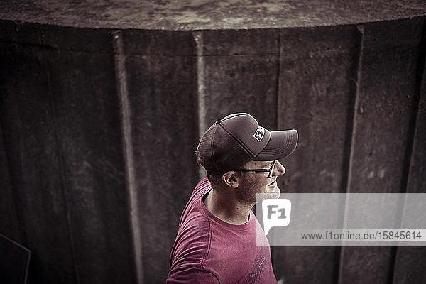 Männlicher Junglandwirt steht mit aufgesetztem Deckel und Brille lächelnd am Wassertank