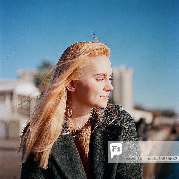 Eine schöne Frau sitzt allein auf dem Pier und lächelt