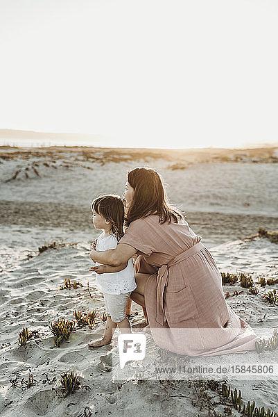 Seitlicher Virew der Mutter umarmt Kleinkindzwillinge am Strand