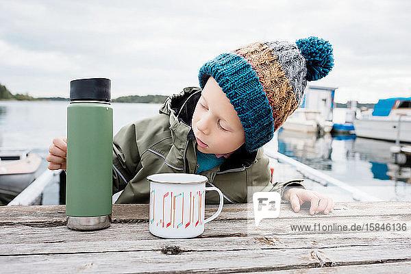 Junge saß am Strand und trank heiße Schokolade auf einer Picknickbank