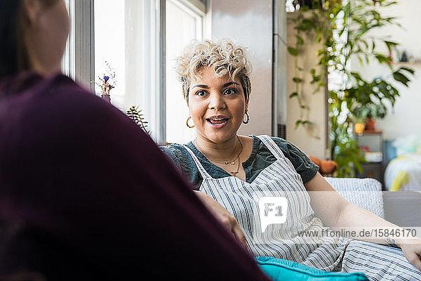 Mittlere erwachsene Frau  die zu Hause auf dem Sofa sitzend mit einem Freund spricht