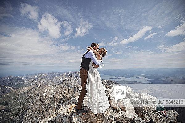 Das frisch verheiratete Paar teilt den ersten Kuss auf dem Gipfel des Grand Teton Wyoming