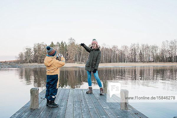 Mutter  die für ihren Sohn posiert  um beim Spielen am Meer ein Foto zu machen