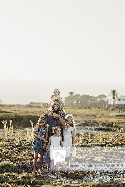 Lifestyle portrait of mother with young girls smiling at beach sunset