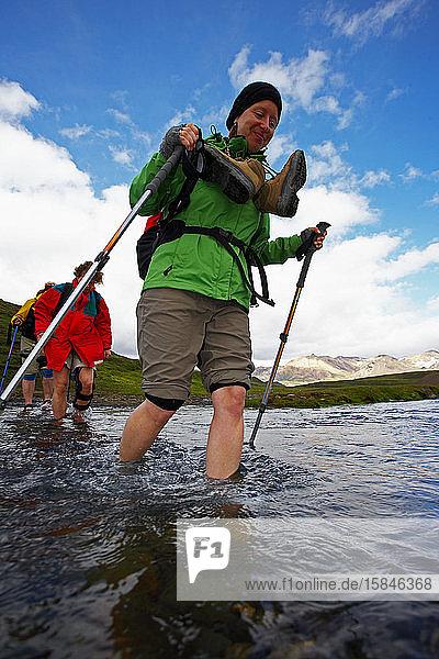 Gruppe von Wanderern überquert Fluss auf dem Laugavegur-Wanderweg