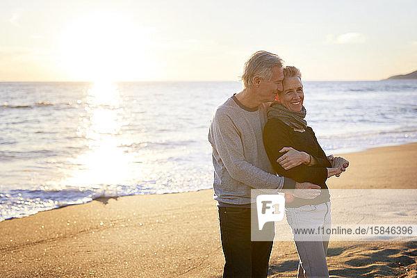 Zärtliches älteres Ehepaar  das bei Sonnenuntergang am Strand gegen den Himmel steht