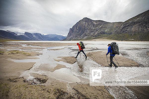 Zwei Rucksacktouristen überqueren Ströme am Akshayak-Pass  Baffin Island.