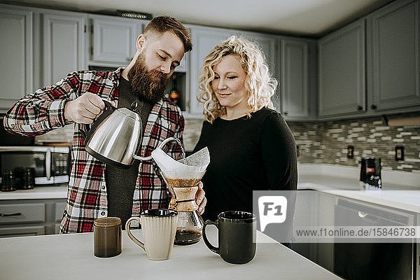 Mann gießt heißes Wasser in den Kaffee  den er übergießt  während die Frau zuschaut