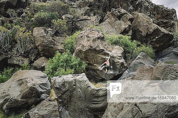 Mann klettert auf einen Felsbrocken inmitten einer Vulkanlandschaft
