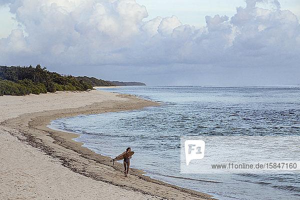 Junge Frau mit Surfbrett am Strand spazieren gehen