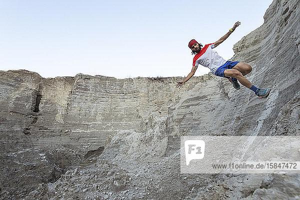 Ein Mann führt einen Mauerritt durch  während er auf sandigem Gelände läuft