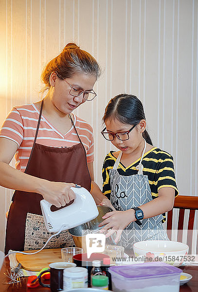 Mother and daughter mixing the ingredients in metal bowl