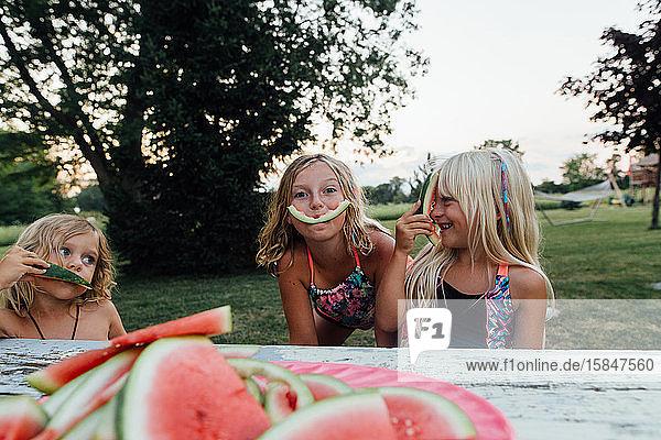 Kleine Kinder  die im Sommer beim Verzehr von Wassermelonen im Freien albern sind Kleine Kinder, die im Sommer beim Verzehr von Wassermelonen im Freien albern sind