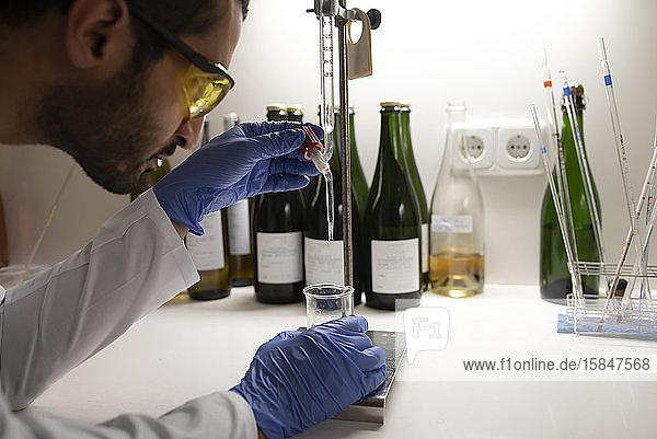 Nahaufnahme des Laboranten durch Auflegen einer Probe auf ein Becherglas.