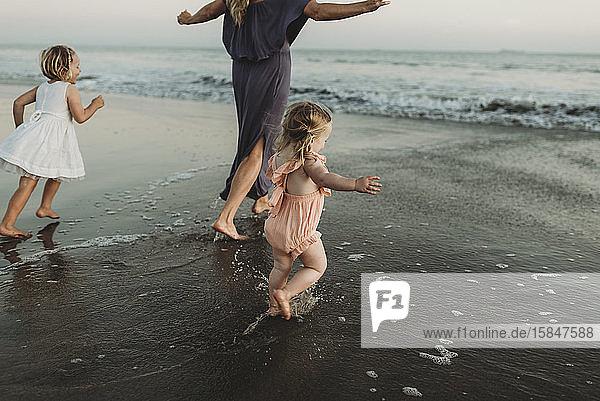 Hinteransicht einer jungen Familie  die bei Sonnenuntergang auf das Meer zugeht