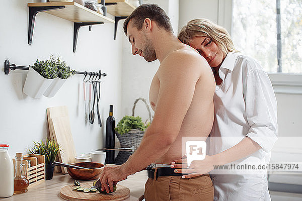 Loving joyful couple embracing and cooking together in the kitchen