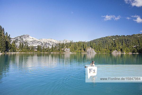Aktive Frau paddelt stehendes Paddelbrett auf blauem See.