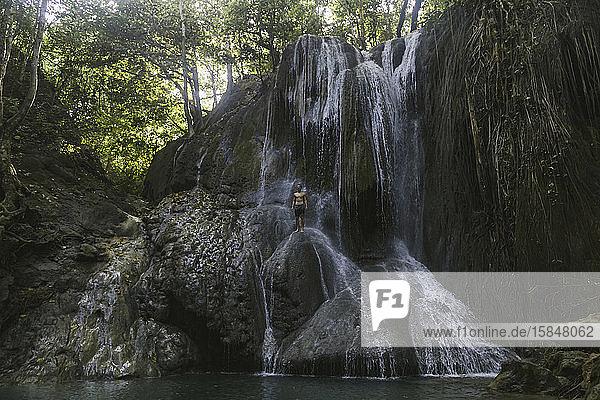 Junger Mann klettert auf Wasserfall