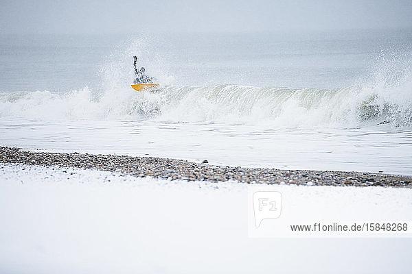Mann surft im Winterschnee
