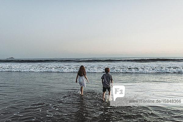 Geschwister  die bei Sonnenuntergang in den Ozean gehen und auf den Horizont starren