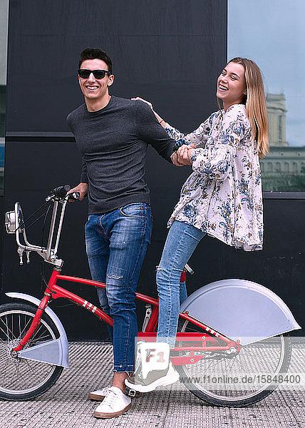Junges befreundetes Paar fährt Fahrrad und hat Spaß auf einer Straße in der Stadt