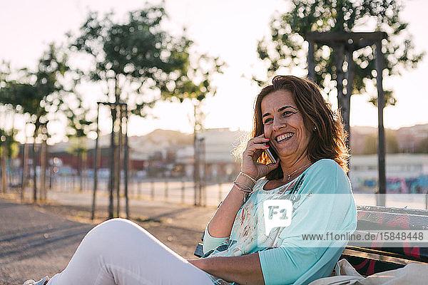 Frau  die telefoniert  während sie auf einer Parkbank sitzt.