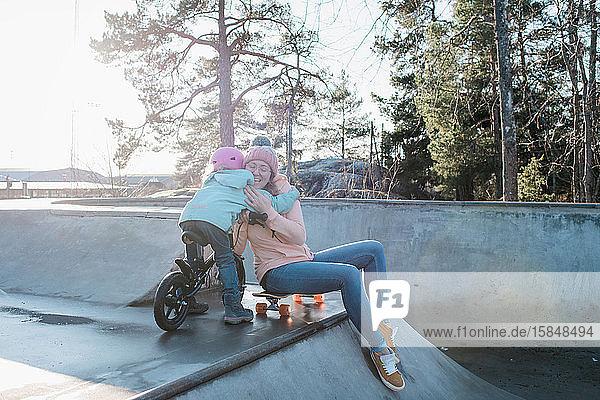 Umarmung der Mutter und ihrer Tochter beim Spielen in einem Skatepark