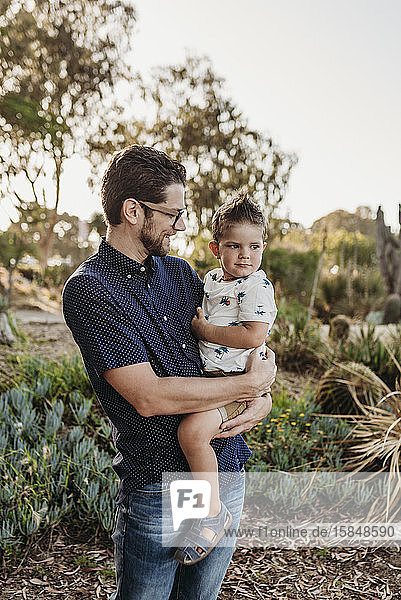 Portrait of dad holding toddler boy and looking at him in sunny garden