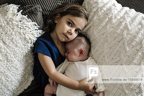Serious 4 yr old girl with cherub lips holding sleeping newborn baby Serious 4 yr old girl with cherub lips holding sleeping newborn baby