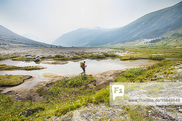 Seitenansicht eines Wanderers mit Rucksack im üppigen Tal
