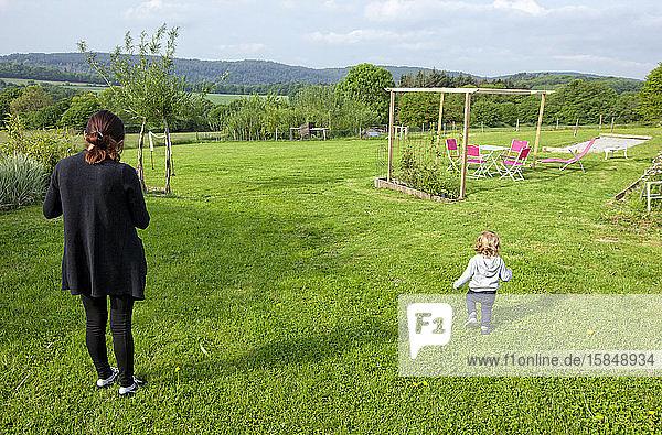 ein kleiner Junge und seine Mutter amüsieren sich auf einer grünen Wiese auf dem Land  Caurel Bretagne  Frankreich.
