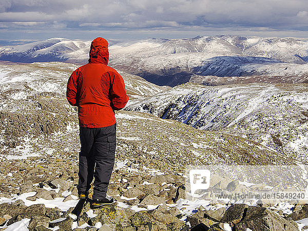 Ein Bergwanderer auf dem Gipfel des Scafell Pike  dem höchsten Berg Englands  Lake District  Großbritannien  mit Blick auf die Helvellyn Range in der Ferne.