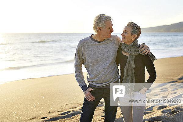 Glückliches älteres Ehepaar am Strand bei Sonnenuntergang