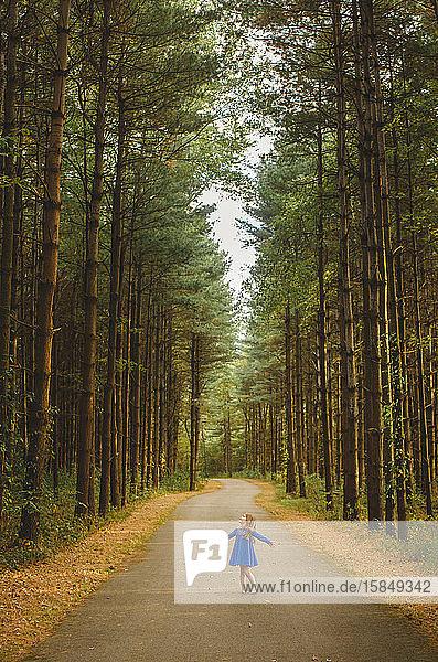 Ein kleines Mädchen wirbelt in einem blauen Kleid in einem magischen Kiefernwald