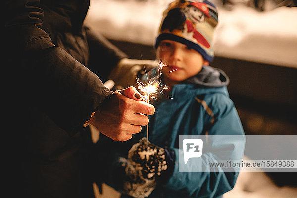 Mutter zündet Wunderkerze an  die ihr Sohn im Winter im Freien hält