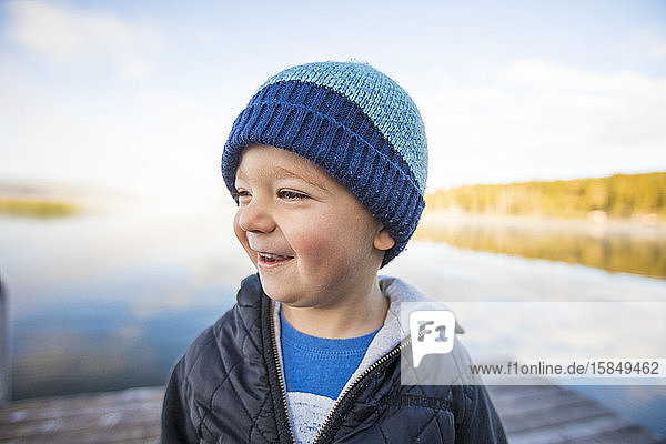 Portrait of young boy laughing on dock.