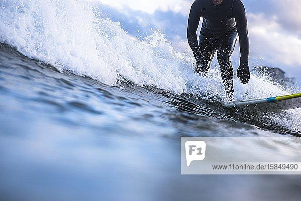 Mann surft am Wintertag bei Sonnenuntergang