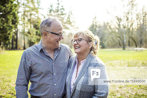 Elderly couple laughing and smiling together outdoors.
