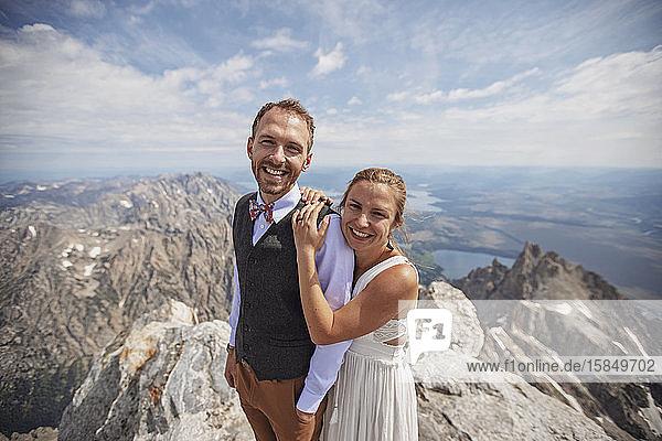 Glückliche Braut und Bräutigam lächeln nach der Heirat auf dem Berggipfel