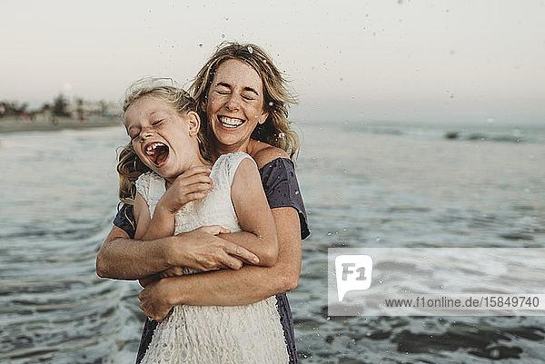 Mutter umarmt junges Mädchen mit Sommersprossen im Meer