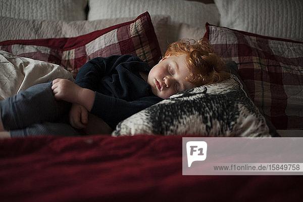 Kleinkind Junge 1-2 Jahre alt schläft auf Kissen im Bett mit roter Bettwäsche