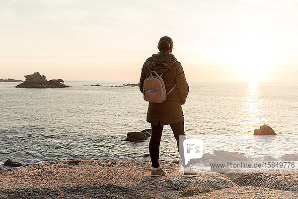 Frau an der Küste  die den Sonnenuntergang beobachtet. Ribeira  Spanien