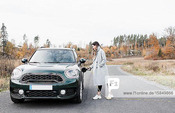 Frau  die auf dem Land ihr Elektroauto Mini Countryman einsteckt