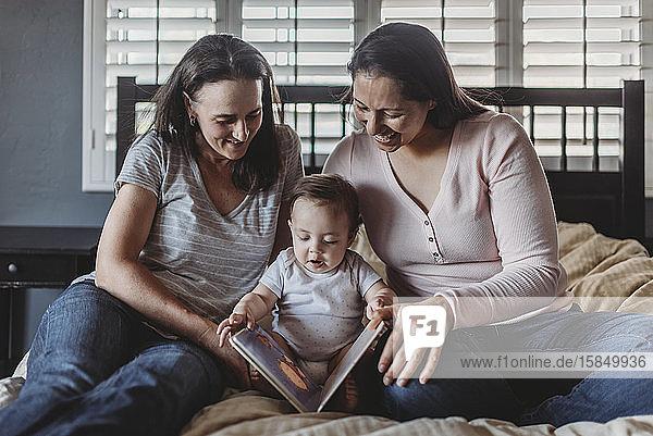 Lächelnde gleichgeschlechtliche Eltern lesen mit dem Baby  während sie auf dem Bett sitzen
