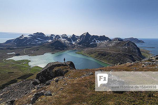 Weibliche Wanderin mit Blick auf das farbenprächtige Wasser des Flakstadpollen und die umliegende Berglandschaft  Flakstadøy  Lofoten-Inseln  Norwegen