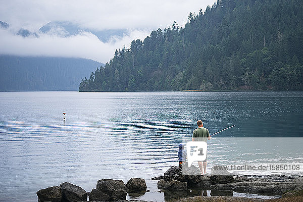 Vater und Sohn beim Angeln am Rand eines malerischen Sees