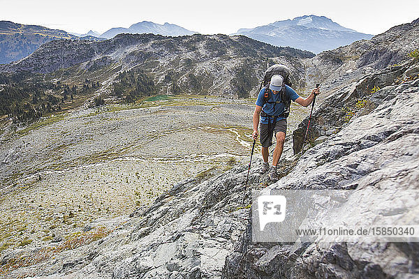 Rucksacktourist wandert über den Talhang in den Bergen in der Nähe von Whistler.